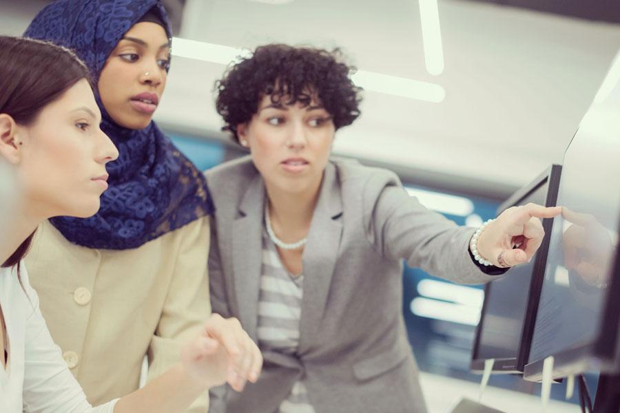 Three Females Looking At A Monitor